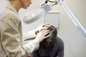 man having his scalp checked